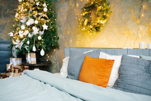 Schlafzimmer mit girlanden aus lichtern dekoriert, um weihnachten zu feiern Premium Fotos