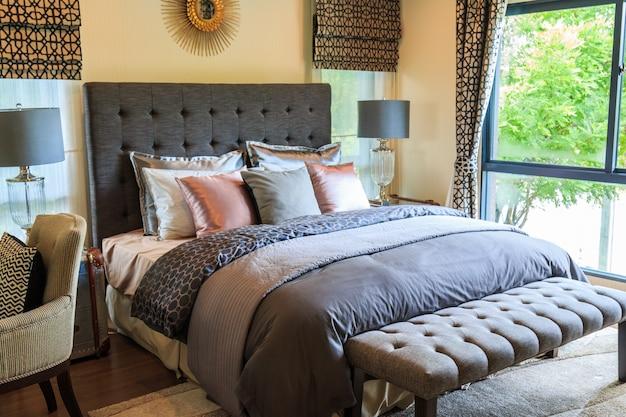 schlafzimmer mit vielen kissen auf dem bett und lampe mit vorhang und jalousien download der. Black Bedroom Furniture Sets. Home Design Ideas