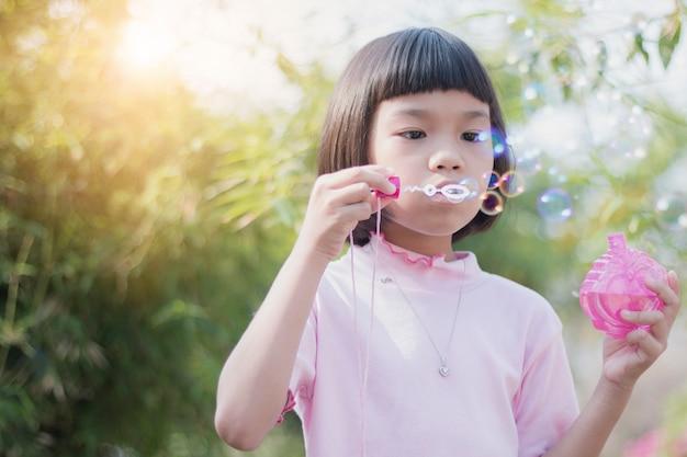 Schlagblasen des lustigen asiatischen kindes im park Premium Fotos