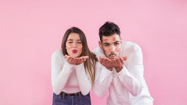 Schlagküsse der jungen paare auf rosa hintergrund Kostenlose Fotos