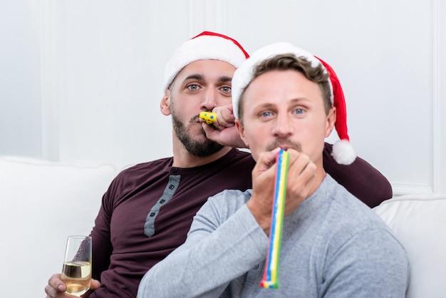 Schlagparteihörner der homosexuellen paare, die zu hause weihnachten feiern Premium Fotos