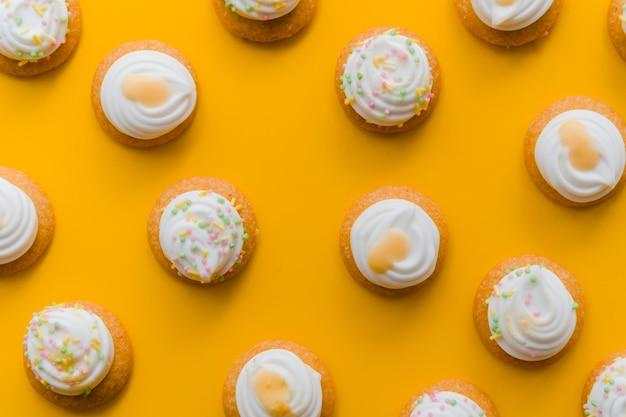 Schlagsahne über kleinem kuchen auf einem gelben hintergrund Kostenlose Fotos
