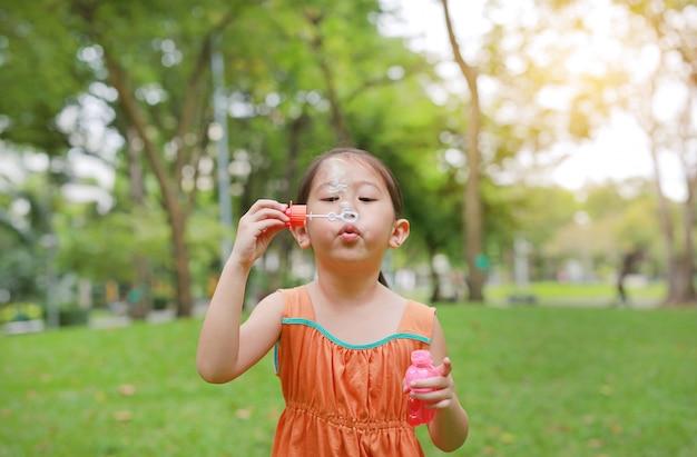 Schlagseifenblasen des entzückenden kleinen asiatischen kindermädchens im grünen garten. Premium Fotos