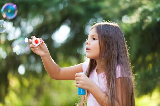 Schlagseifenblasen des kindermädchens im freien Premium Fotos