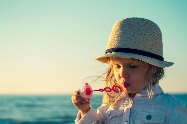 Schlagseifenblasen des kleinen mädchens in dem meer. getönten foto Premium Fotos