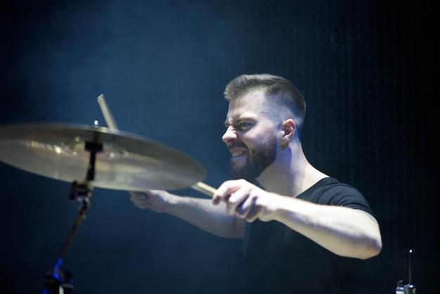 Schlagzeuger in einer kappe und in kopfhörern spielt trommeln bei einem konzert unter weißem licht in einem rauch Premium Fotos