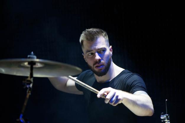 Schlagzeuger in einer kappe und in kopfhörern spielt trommeln bei einem konzert Premium Fotos