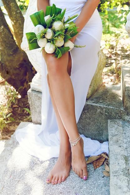 Schlanke bräunungsfrau, die schönen exotischen hochzeitsstrauß mit weißen lotusblumen hält und im park mit exotischen plänen in thailand aufwirft. Kostenlose Fotos