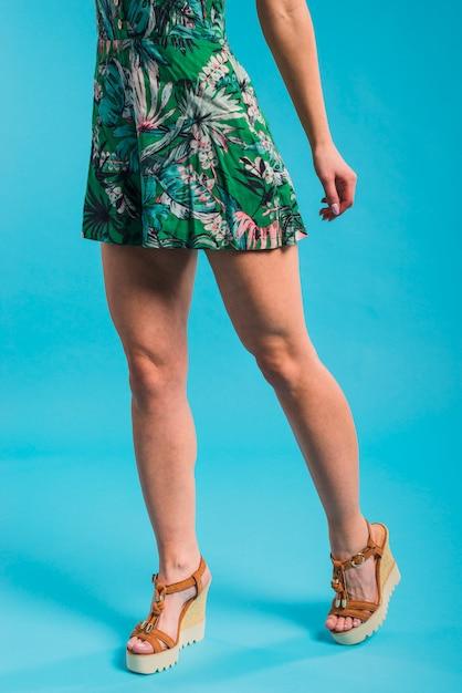 Schlanke junge frau, die in geblühtem kleid aufwirft Kostenlose Fotos