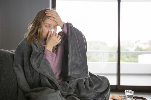 Schlanke nase der kranken frau mit der serviette, hand auf kopf anhalten Kostenlose Fotos