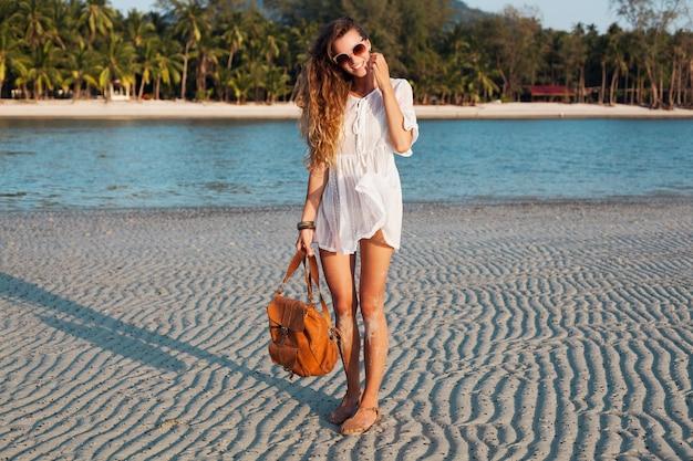Schlanke schöne frau im weißen baumwollkleid, das auf tropischem strand auf sonnenuntergang hält, der lederrucksack hält. Kostenlose Fotos