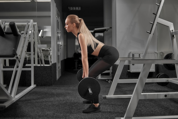 Schlanke sportlerin macht kniebeugen mit langhantel. Premium Fotos