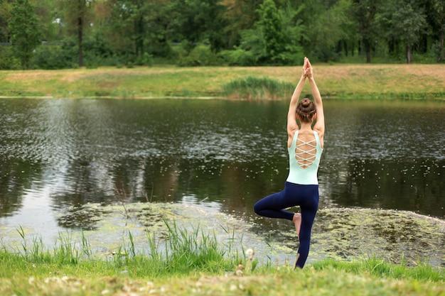 Schlanker junger brunettejogi führt komplexe yogaübung auf grünem gras im sommer durch Premium Fotos