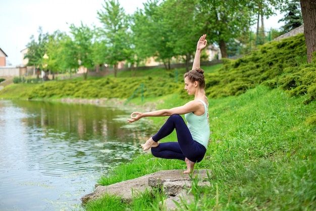 Schlanker junger brunettejogi führt schwierige yogaübungen auf dem grünen gras im sommer vor dem hintergrund der natur durch Premium Fotos