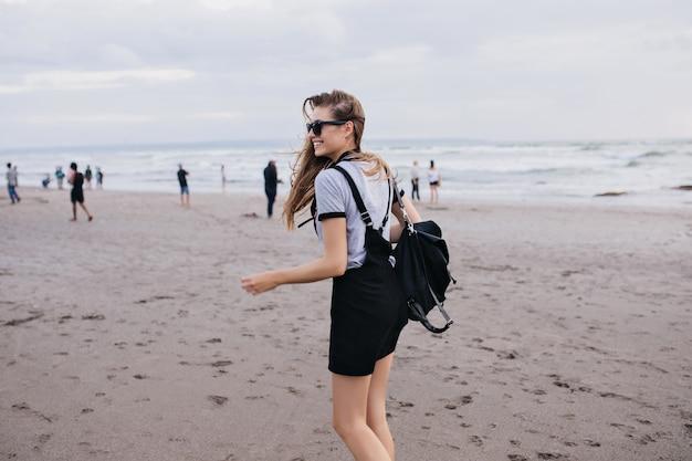 Schlankes blasses mädchen mit schwarzem rucksack, der mit glücklichem lächeln um strand geht. außenaufnahme der herrlichen dame, die spaß nahe meer in kaltem tag hat. Kostenlose Fotos