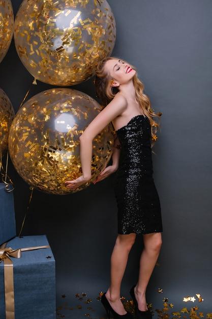 Schlankes europäisches mädchen trägt elegante schuhe, die mit partyballons tanzen und in ihrem geburtstag lächeln. innenfoto der kühlen blonden frau, die mit geschlossenen augen nahe geschenken steht. Kostenlose Fotos