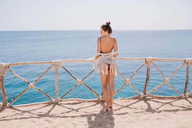 Schlankes gebräuntes mädchen mit niedlicher frisur in gestrickter kleidung, die auf terrasse steht und das meer betrachtet. erstaunliche junge frau, die meerblick in den sommerferien genießt und vor wasser aufwirft Kostenlose Fotos