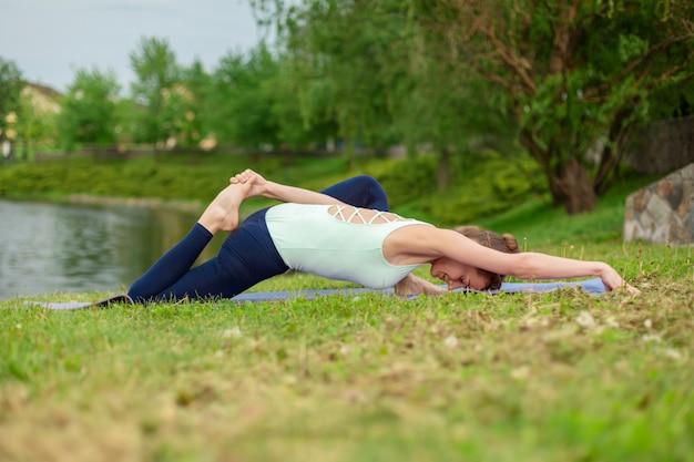 Schlankes kaukasisches brunettemädchen, das yoga im sommer auf einem grünen rasen durch den fluss tut Premium Fotos