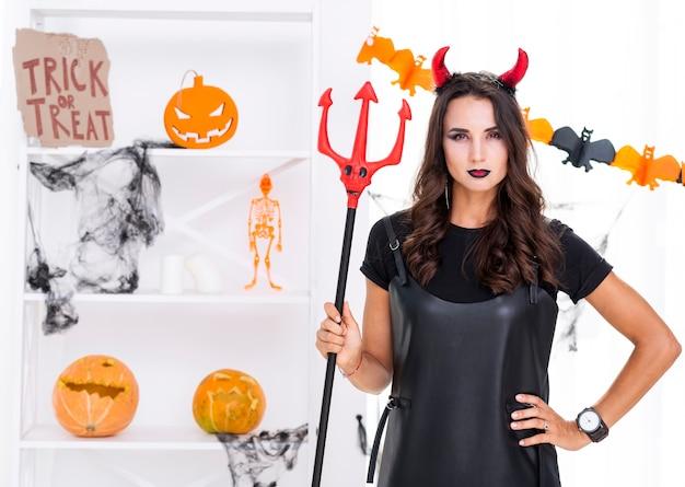Schlechte frau mit dem dreizack, der für halloween aufwirft Kostenlose Fotos