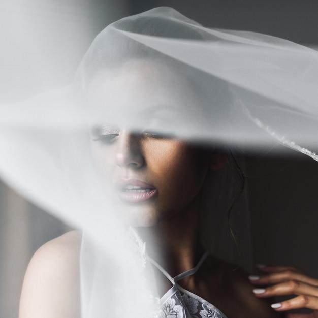 Schleier bedeckt das zarte gesicht der braut, während sie vor einem fenster steht Kostenlose Fotos