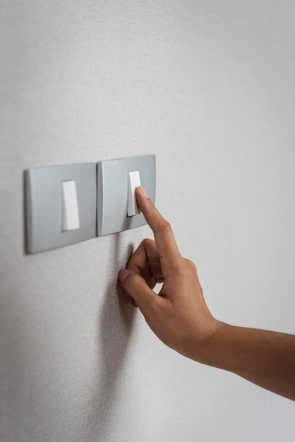 Schließen sie die hand, die an grauen lichtschaltern mit beschaffenheitshintergrund ein- oder ausschaltet. Premium Fotos