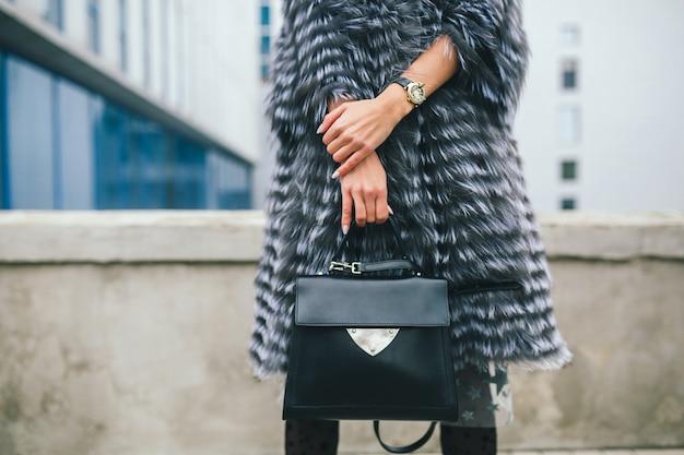 Schließen sie herauf accessoires details der stilvollen frau, die in der stadt im warmen pelzmantel hält schwarze ledertasche, wintersaison, Kostenlose Fotos