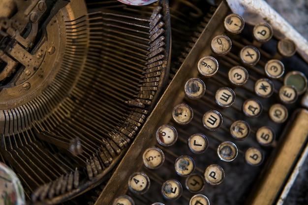 Schließen sie herauf ansicht auf einem alten schmutzigen gebrochenen antiken schreibmaschinenmaschinenschlüssel mit kyrillischen symbolbuchstaben. Premium Fotos