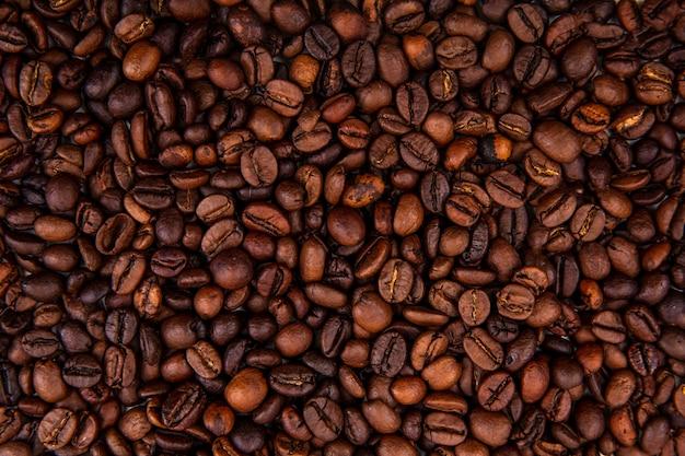 Schließen sie herauf ansicht der dunklen frischen gerösteten kaffeebohnen auf kaffeebohnenhintergrund Kostenlose Fotos