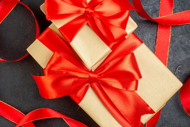 Schließen sie herauf ansicht der gestapelten schönen geschenke mit rotem band auf dunklem hintergrund Kostenlose Fotos