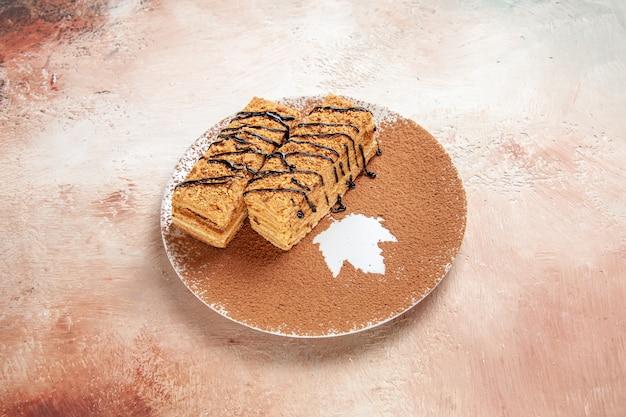 Schließen sie herauf ansicht der leckeren desserts, die mit schokoladensyrop für eine person auf buntem tisch verziert werden Kostenlose Fotos