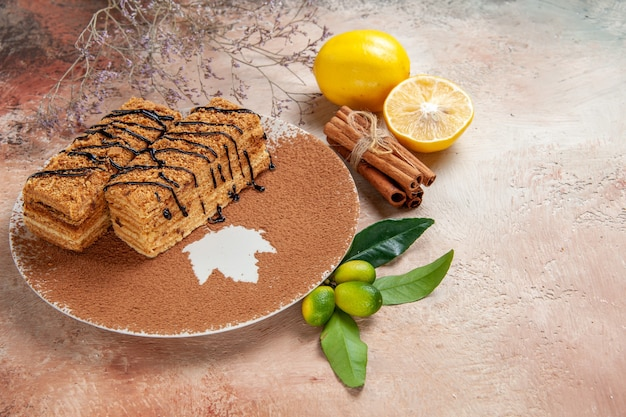 Schließen sie herauf ansicht der leckeren desserts, die mit schokoladensyrop und zitrone auf buntem tisch verziert werden Kostenlose Fotos