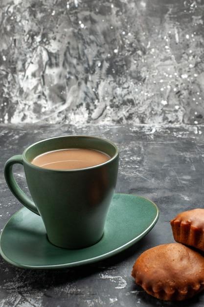 Schließen sie herauf ansicht des köstlichen kaffees und zwei kuchen in einer grünen tasse auf grau Kostenlose Fotos