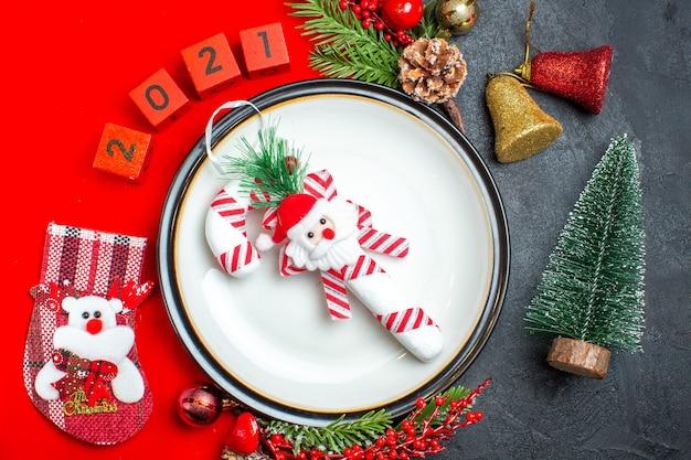 Schließen sie herauf ansicht des neujahrshintergrundes mit abendessenplatte-dekorationszubehör tannenzweigen und nummeriert weihnachtssocke auf einer roten serviette neben weihnachtsbaum auf einem schwarzen tisch Kostenlose Fotos