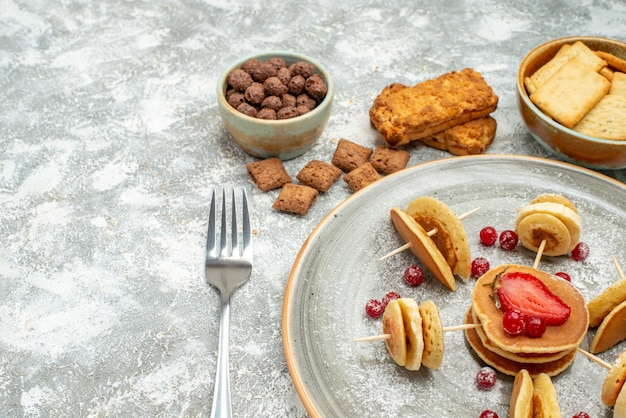 Schließen sie herauf ansicht von buttermilchpfannkuchen auf schneidebrett mit schokolade und keksen auf blau Kostenlose Fotos
