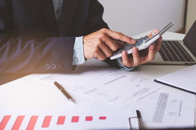 Schließen sie herauf ansichthände des geschäftsmannes unter verwendung des taschenrechners und buchhaltung mit diagramm und dokumenten auf dem tisch tun. Premium Fotos