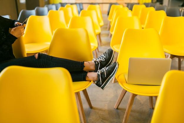 Schließen sie herauf beine der jungen stilvollen frau, die im hörsaal mit laptop, klassenzimmer mit vielen gelben stühlen, schuhen turnschuhe, schuhe modetrend sitzt Kostenlose Fotos