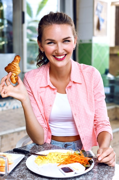 Schließen sie herauf bild der glücklichen lächelnden frau genießen sie ihr morgendliches französisches frühstück auf offener caféterrasse, leckeres bio-lebensmittel. französisch croissant in der hand halten. Kostenlose Fotos