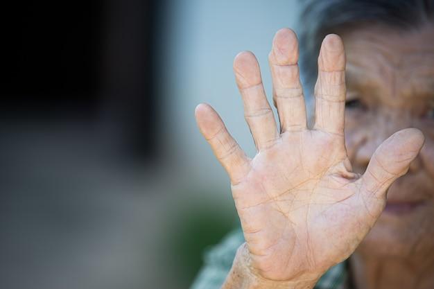 Schließen sie herauf bild der hand der alten frau, die antisymbol zeigt Kostenlose Fotos