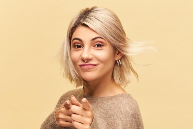 Schließen sie herauf bild des schönen hübschen mädchens mit unordentlich blondem haar und nasenring lächelnd und zeigefinger zeigend, herausforderung zu ihnen herauswerfend. körpersprache, zeichen, symbol und gestenkonzept Kostenlose Fotos
