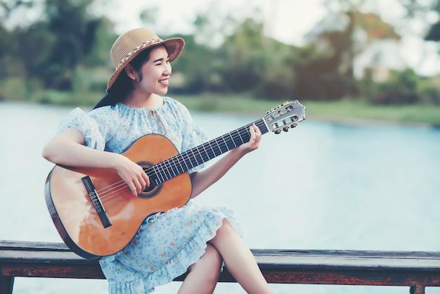 Schließen sie herauf bilder der hände der frau, die akustikgitarre spielen Kostenlose Fotos