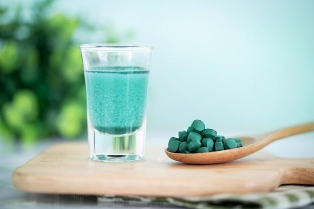 Schließen sie herauf blaue spirulina smoothie- und spirulinapillen des strengen vegetariers, eine gesunde superfood-diät und ein detoxnahrungskonzept Premium Fotos