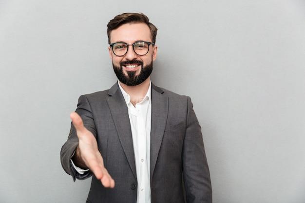 Schließen sie herauf das porträt des freundlichen netten mannes in den brillen, die auf kamera mit dem aufrichtigen lächeln schauen und den händedruck anbieten, der über grau lokalisiert wird Kostenlose Fotos