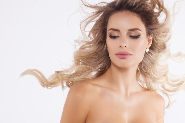 Schließen sie herauf das porträt des schönen blonden modells, das auf weiß lokalisiert wird Premium Fotos