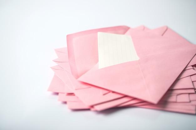 Schließen sie herauf das stapeln der rosa umschläge und des briefbriefpapiers auf weißem hintergrund Premium Fotos