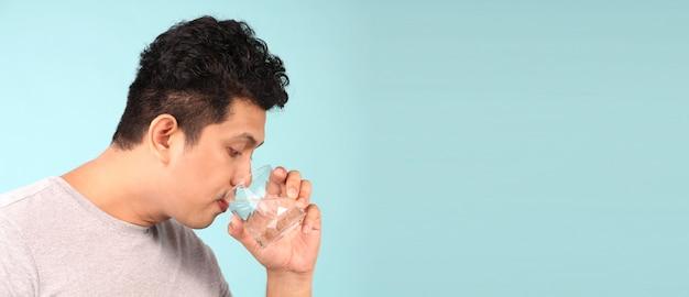 Schließen sie herauf das trinkwasser des mannes, das auf dem blauen hintergrund lokalisiert wird Premium Fotos
