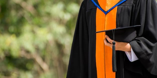 Schließen sie herauf den absolvent, der einen hut hält. konzept erfolg ausbildung an der universität Premium Fotos