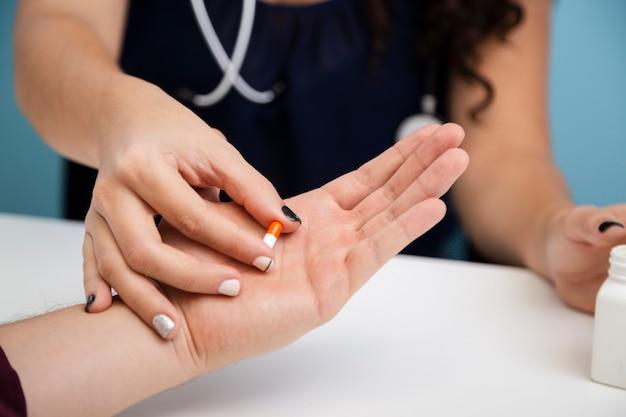 Schließen sie herauf den doktor, der eine pille gibt Kostenlose Fotos