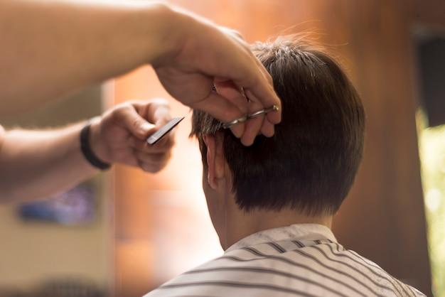 Schließen sie herauf den hinteren ansichtmann, der einen haarschnitt erhält Kostenlose Fotos
