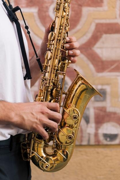 Schließen sie herauf den mann, der das saxophon spielt Kostenlose Fotos