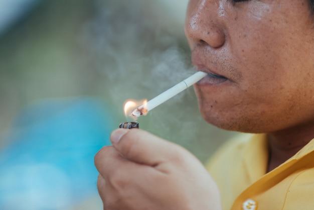 Schließen sie herauf den mann, der eine zigarette raucht Kostenlose Fotos